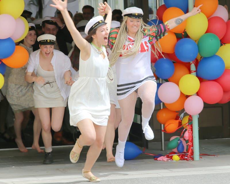 Lyckliga tonårs- flickor som bär avläggande av examen, caps spring ut från sch arkivfoto