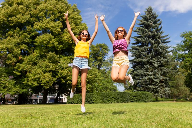 Lyckliga tonårs- flickor som hoppar på sommar, parkerar royaltyfria bilder