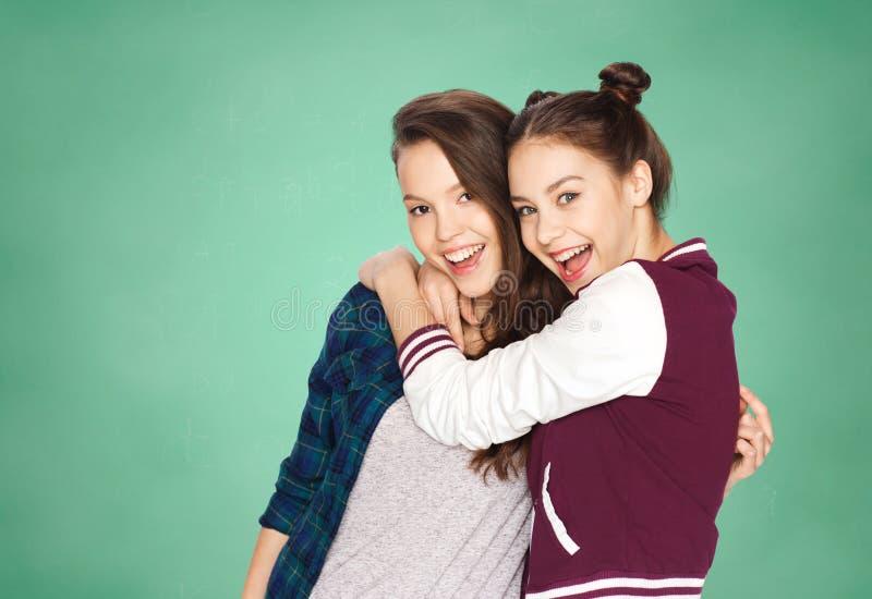 Lyckliga tonårs- flickor som kramar över grönt bräde fotografering för bildbyråer