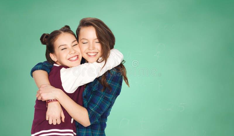 Lyckliga tonårs- flickor som kramar över grönt bräde arkivbild