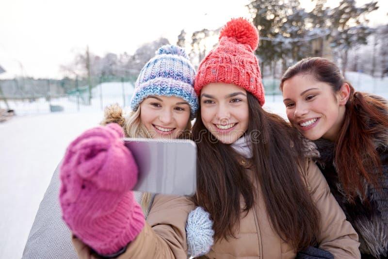 Lyckliga tonårs- flickor som tar selfie med smartphonen arkivfoton