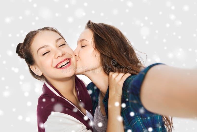 Lyckliga tonårs- flickor som tar selfie och att kyssa royaltyfria foton