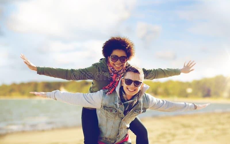 Lyckliga tonårs- par i skuggor som har gyckel på stranden fotografering för bildbyråer