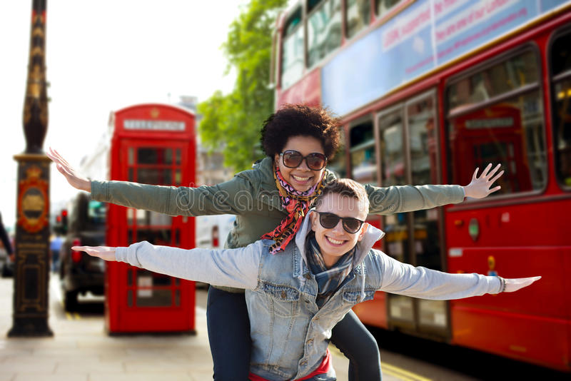 Lyckliga tonårs- par som har gyckel i den london staden royaltyfri foto