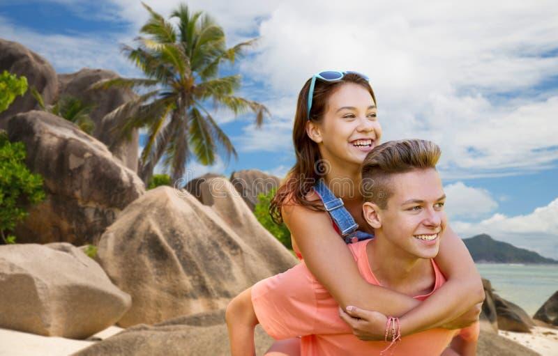 Lyckliga tonårs- par som har gyckel på sommarstranden royaltyfri bild