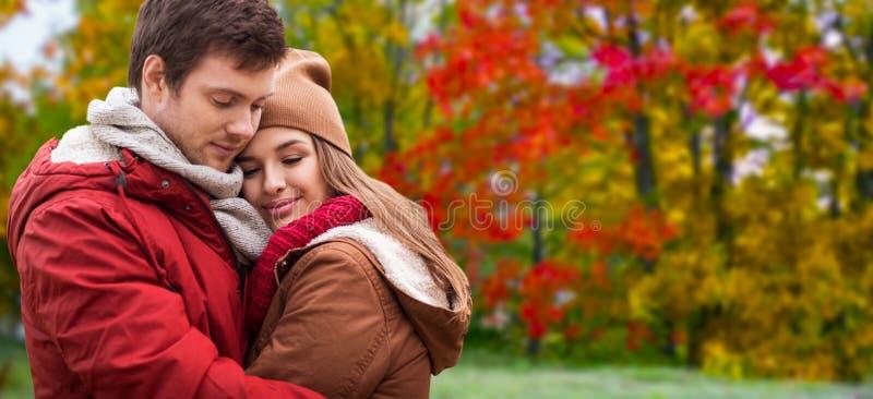 Lyckliga tonårs- par som kramar i höst, parkerar fotografering för bildbyråer