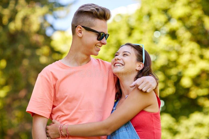 Lyckliga tonårs- par som ser de parkerar in fotografering för bildbyråer