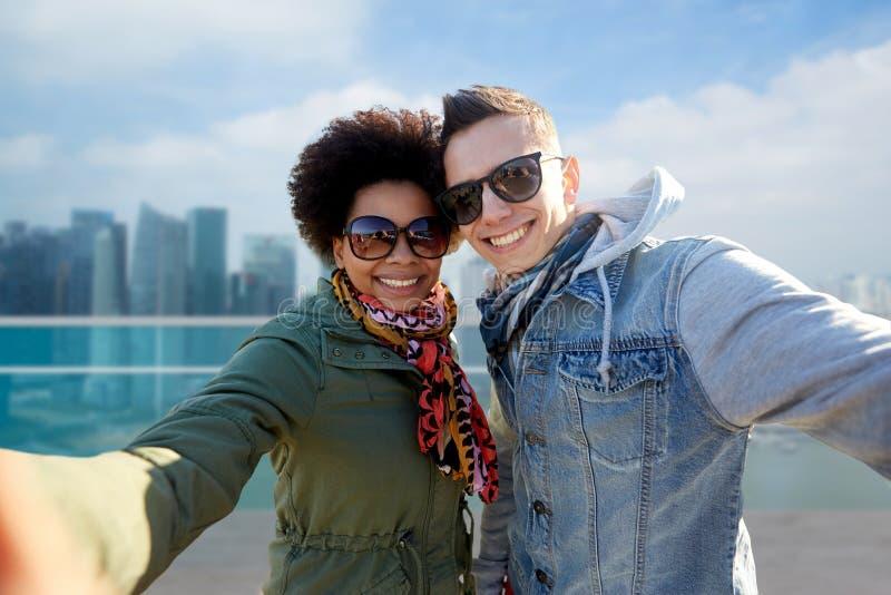 Lyckliga tonårs- par som tar selfie i singapore arkivbilder