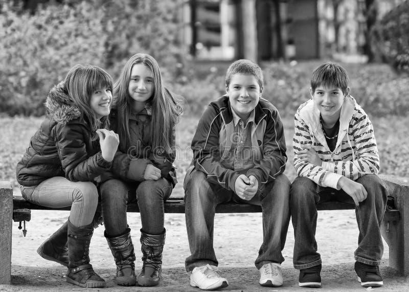 Lyckliga tonårs- pojkar och flickor som sitter ha gyckel i vår, parkerar fotografering för bildbyråer