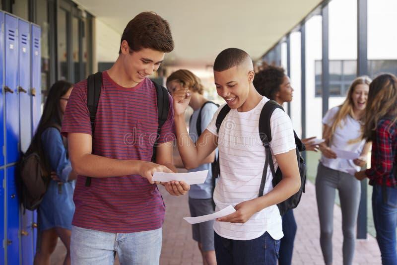 Lyckliga tonårs- pojkar som delar examen, resulterar i skolakorridor royaltyfri foto