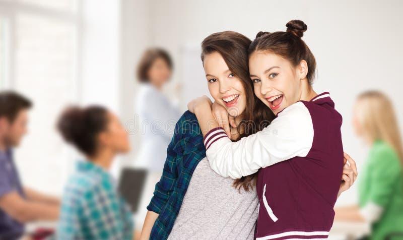 Lyckliga tonårs- studentflickor som kramar på skolan arkivbild