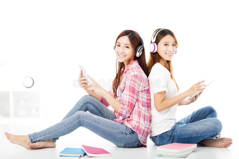 lyckliga tonårs- studentflickor som sitter på golvet royaltyfria foton