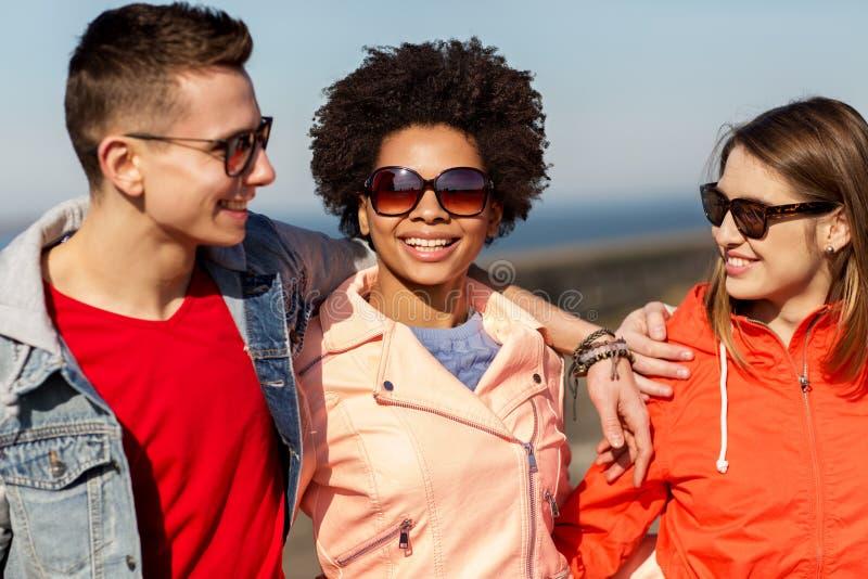 Lyckliga tonårs- vänner i skuggor som talar på gatan arkivfoton
