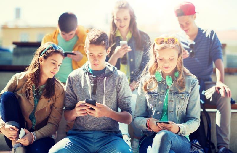 Lyckliga tonårs- vänner med smartphones utomhus royaltyfri foto