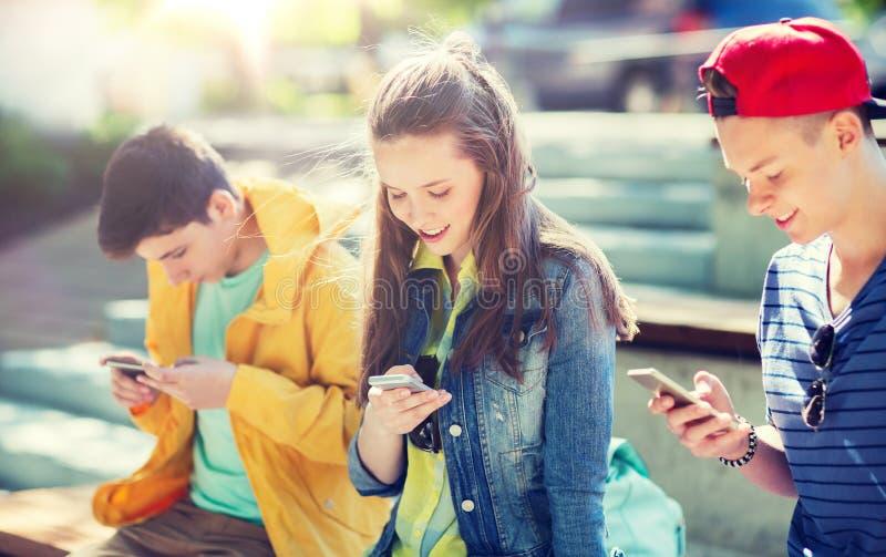 Lyckliga tonårs- vänner med smartphones utomhus arkivfoto