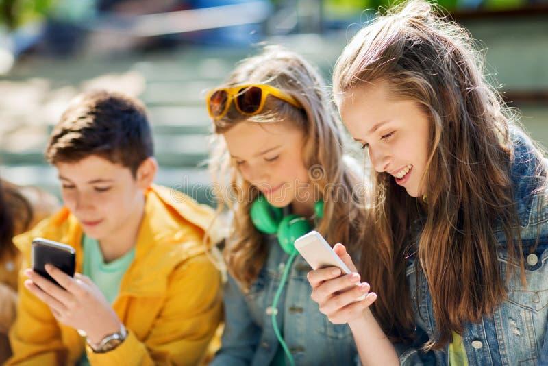 Lyckliga tonårs- vänner med smartphones utomhus arkivfoton