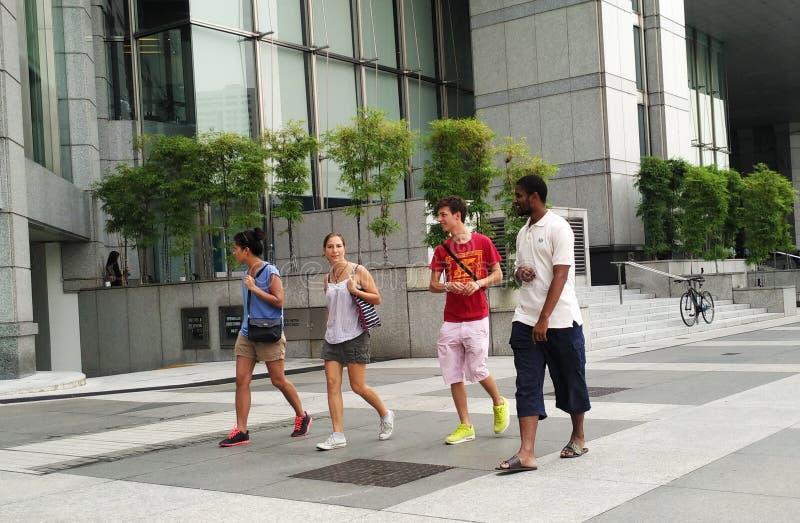 Lyckliga tonårs- vänner som promenerar stadsgatan royaltyfri foto