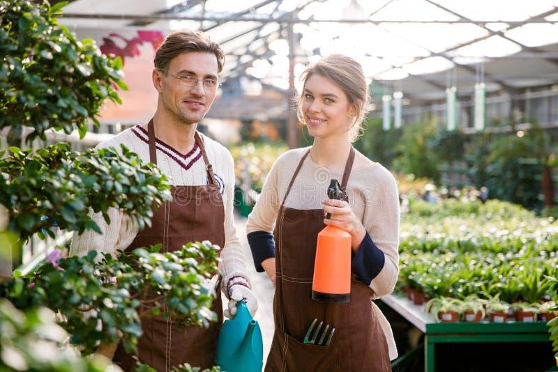 Lyckliga trädgårdsmästare som rymmer att bevattna kan, och pulveriser för att bespruta blommar arkivfoto