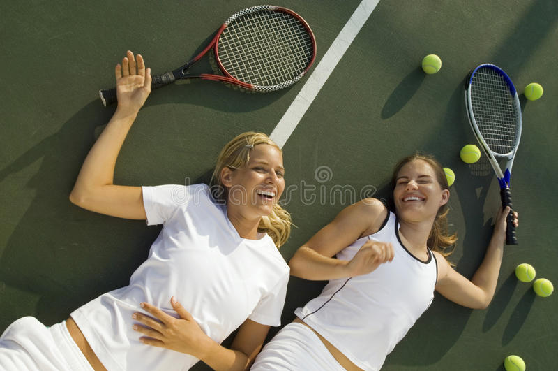 Lyckliga trötta kvinnor som skrattar på tennisbanan royaltyfri fotografi