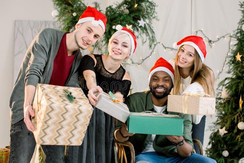 Lyckliga tre Caucasian pojke och flickor och afrikansk pojke som ler och har gyckel på julberöm arkivbild