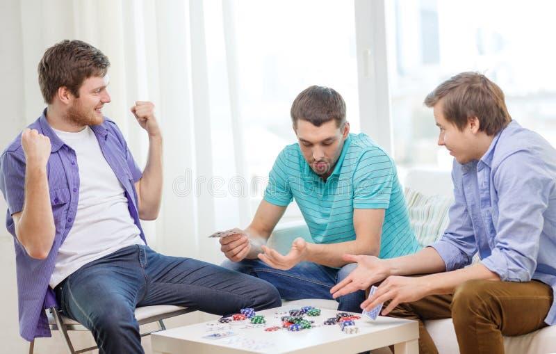 Lyckliga tre manliga vänner som hemma spelar poker royaltyfri foto