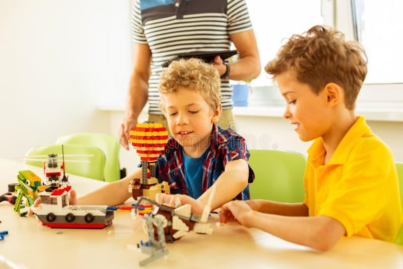 Lyckliga trevliga unga pojkar som tillsammans konstruerar leksaker royaltyfria foton