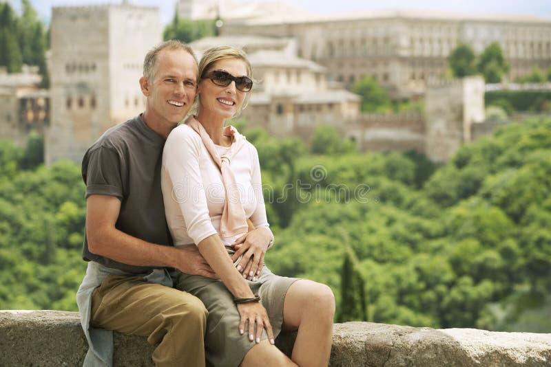 Lyckliga turist- par som poserar på väggen arkivbild