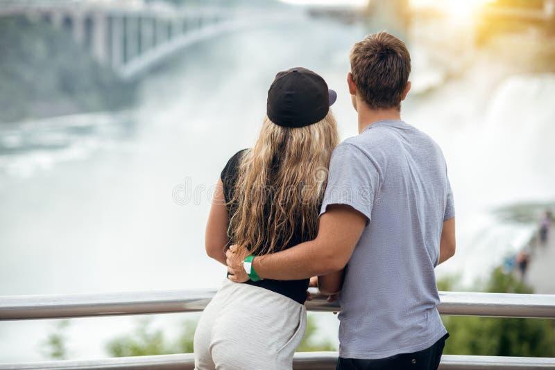 Lyckliga turist- par som tycker om sikten till Niagara Falls under romantisk semester Folk som ser till naturlandskapet på solned royaltyfria bilder