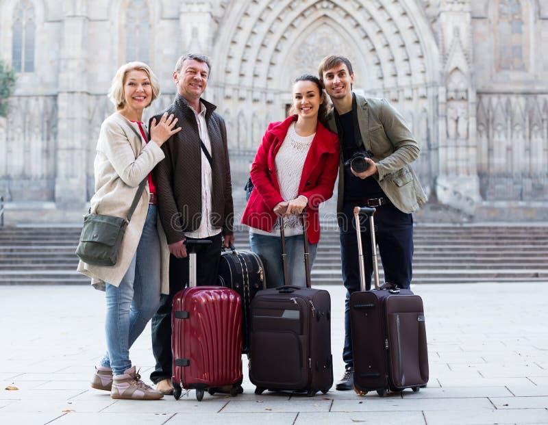Lyckliga turister med bagage poserar på gatan arkivfoto