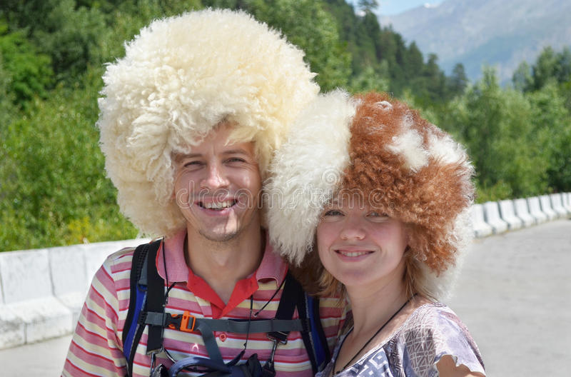 Lyckliga turister som bär roliga fårhattar som står på berget roa royaltyfri foto