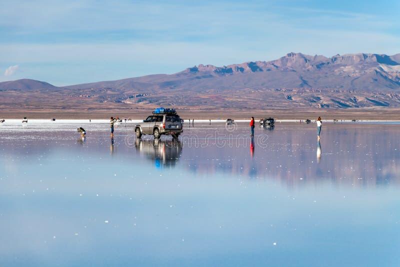 Lyckliga turister tycker om jeepen turnerar aktiviteter saltar in den plana sjön Salar de Uyuni i Bolivia royaltyfri fotografi