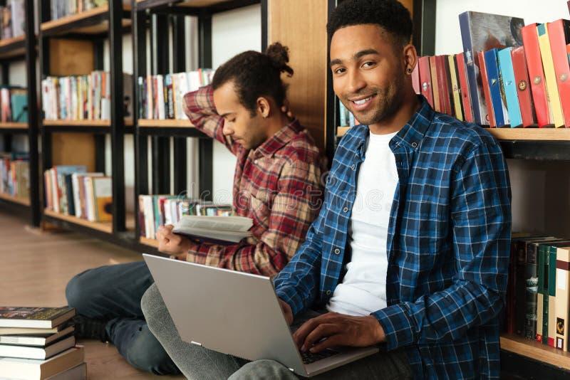 Lyckliga två afrikanska manstudenter som använder bärbar datordatoren arkivbild