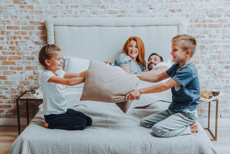 Lyckliga två barn som tillsammans spelar med kudden arkivbild
