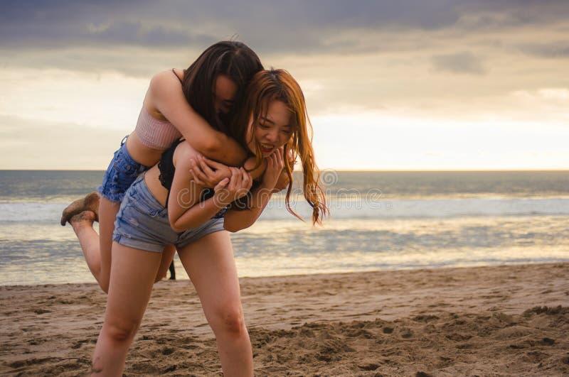 Lyckliga två och attraktiva unga asiatiska kinesiska kvinnaflickvänner eller systrar som har gyckel som spelar i sanden på solned royaltyfria bilder