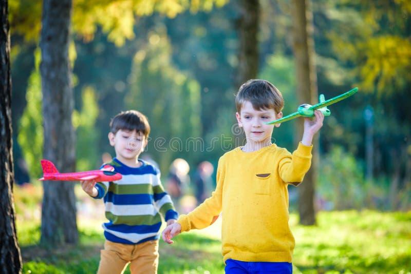 Lyckliga tv? broderungar som spelar med leksakflygplanet mot bl? sommarhimmelbakgrund Pojkar kastar skumniv?n i skogen eller park fotografering för bildbyråer