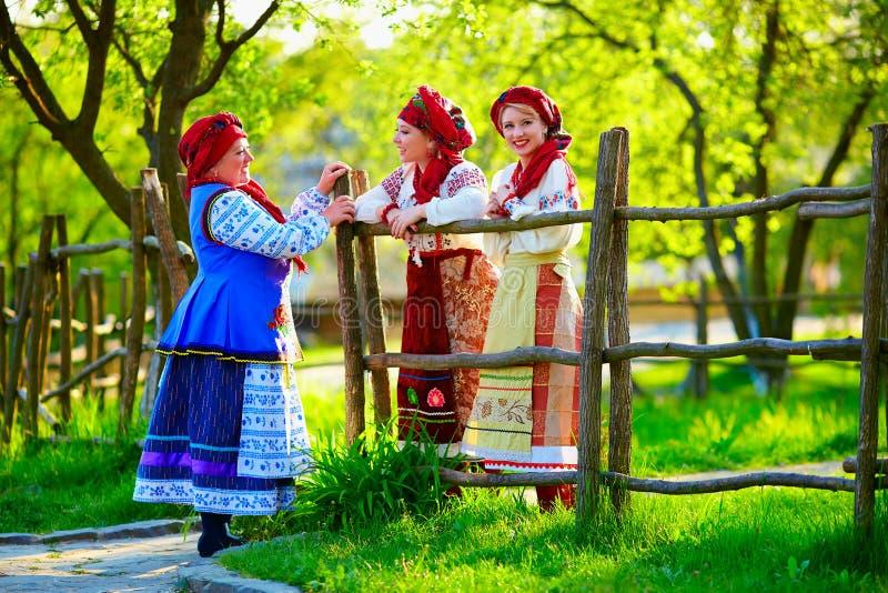 Lyckliga ukrainska kvinnor, iklädda traditionella dräkter som talar på gatan royaltyfri bild