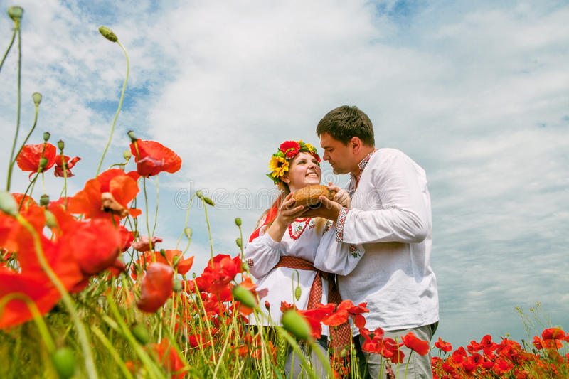 Lyckliga ukrainska par på blomningfältet royaltyfria bilder