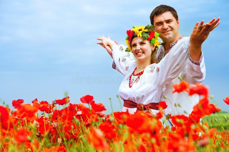 Lyckliga ukrainska par på vallmofält royaltyfri fotografi