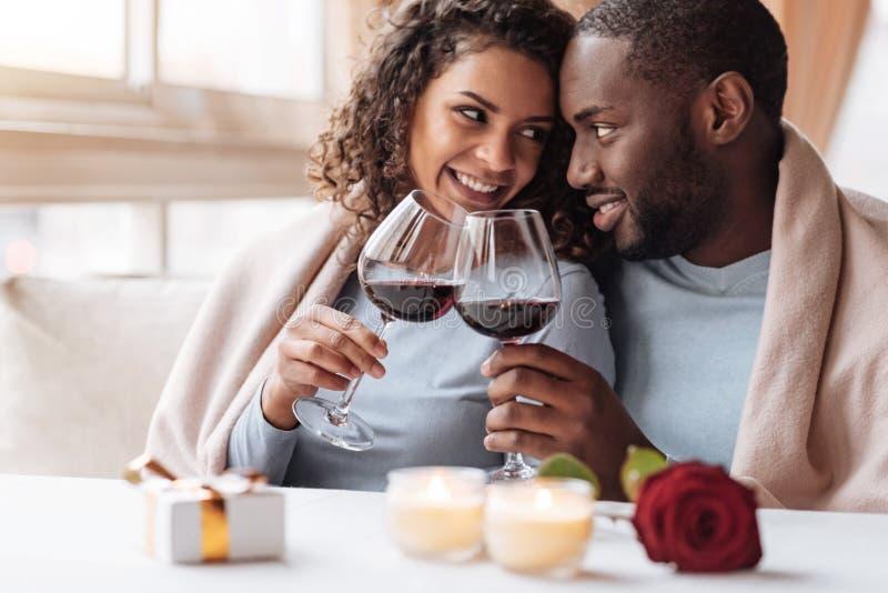 Lyckliga unga afrikansk amerikanpar som dricker vin i restaurangen arkivfoton