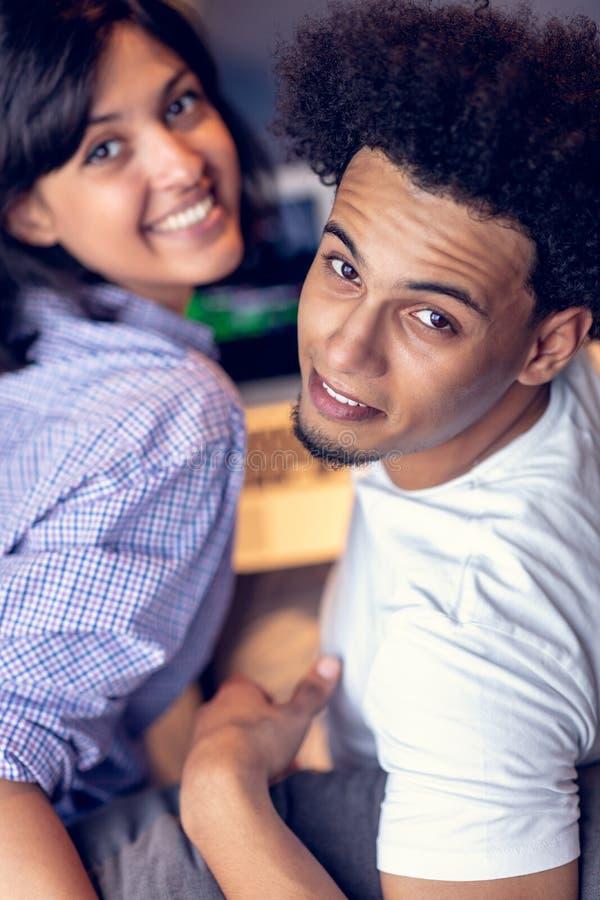Lyckliga unga afrikanska par med bärbar datordatoren royaltyfri bild