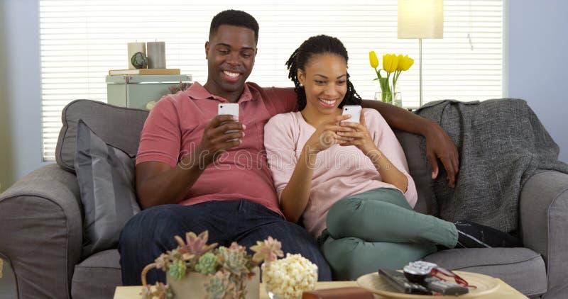 Lyckliga unga afrikanska par som kopplar av på soffan genom att använda smartphones royaltyfri fotografi