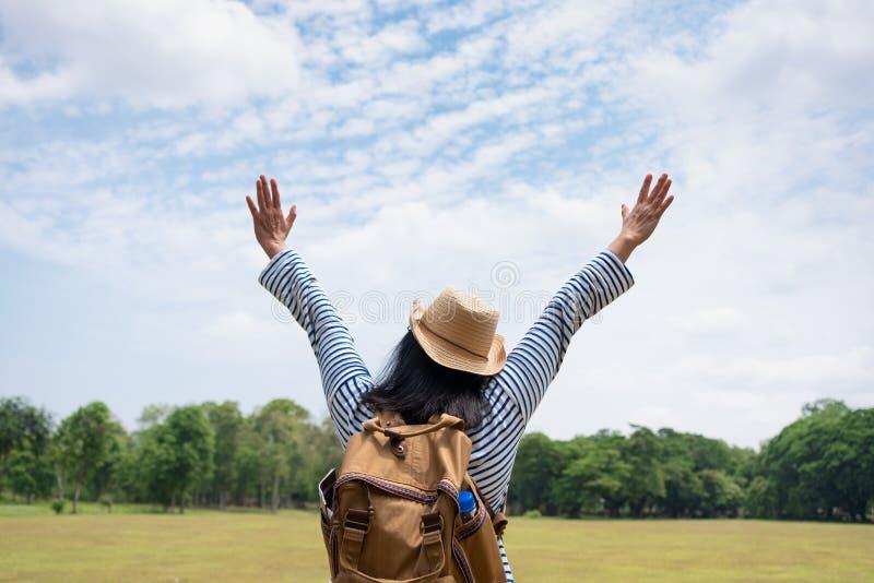 Lyckliga unga armar för handelsresandekvinnafotvandrare upp och tycka om ett härligt av naturen på luft för grönska för gräsfält  royaltyfri foto