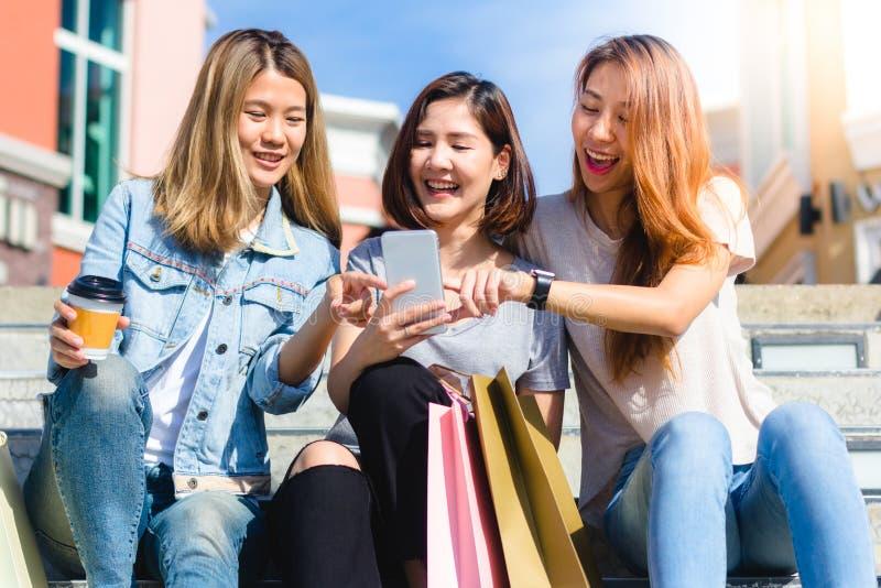 Lyckliga unga asiatiska kvinnor grupperar stadslivsstilen som spelar och pratar sig bland den pastellfärgade byggnadsstaden på he fotografering för bildbyråer