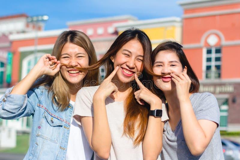 Lyckliga unga asiatiska kvinnor grupperar stadslivsstilen som spelar och pratar sig bland den pastellfärgade byggnadsstaden på he arkivbild