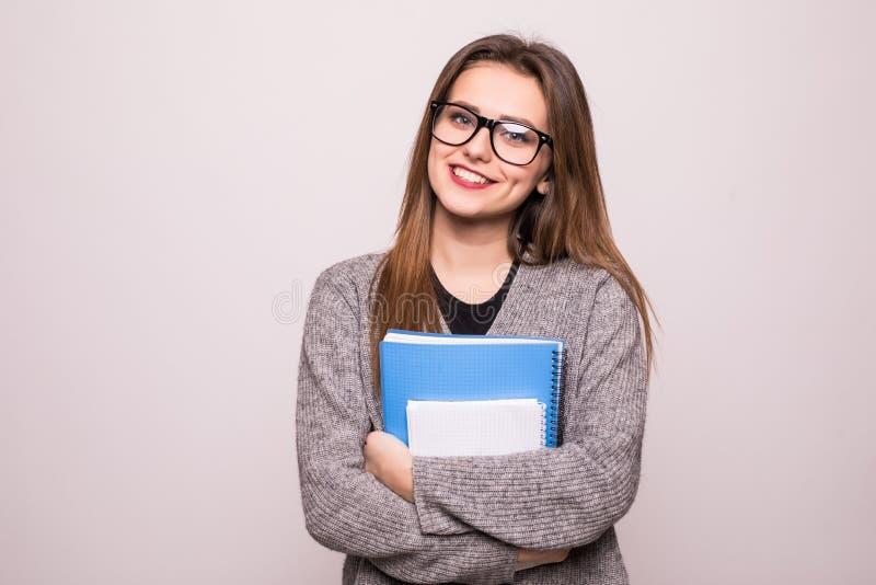 Lyckliga unga böcker för studentflickainnehav som isoleras på vit bakgrund Studie utbildning, kunskap, målbegrepp royaltyfri fotografi