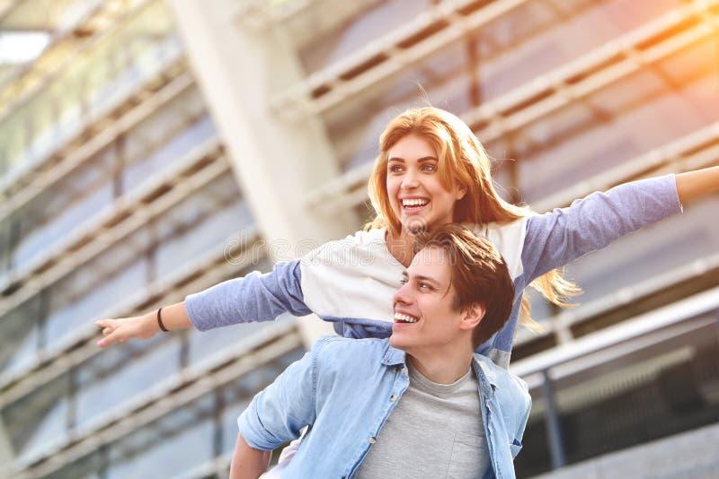 Lyckliga unga caucasian par som har gyckel med ridtur p? axlarna utomhus arkivfoto