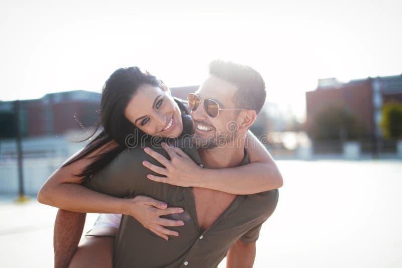 Lyckliga unga caucasian stads- par som gör ridtur på axlarna och ler på det fria arkivbild