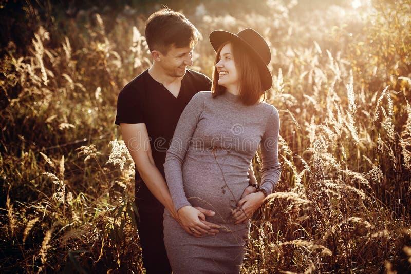 Lyckliga unga föräldrar, mamman och farsan som kramar behandla som ett barn bulan och att le som tycker om härligt ögonblick på s royaltyfri bild