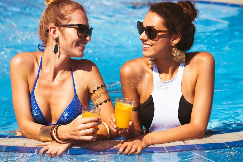 Lyckliga unga flickor med drycker på sommar festar nära pölen royaltyfri fotografi