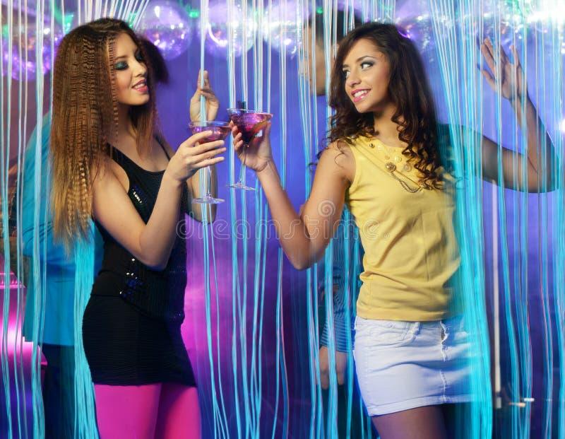 Lyckliga unga flickor på nattklubben fotografering för bildbyråer